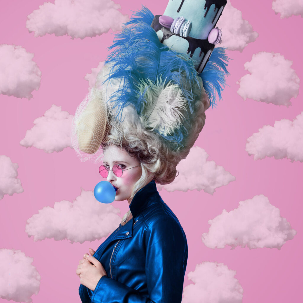 Portrait of rebel woman wearing a big baroque wig and dress and leather jacket, blowing a bubble gum balloon. Standing against pink background.